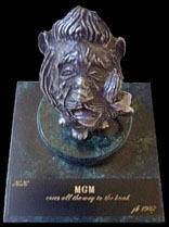 Photo of Wizard of OZ Cowardly lion statuette on a marble base with caption: KK - MGM cries all the way to the bank- 1982